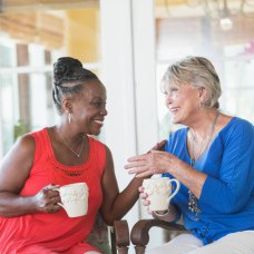 Two senior multi-ethnic woman, one Caucasian and the other African American, sitting on a porch enjoying each other's company. They are facing each other, smiling, talking and drinking coffee.